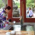 Frau in Kimono an einem Trinkbrunnen in Tokyo